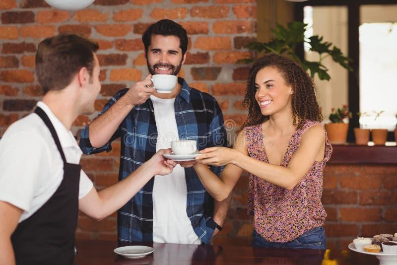 Glimlachende klanten die kop van koffie krijgen stock afbeeldingen