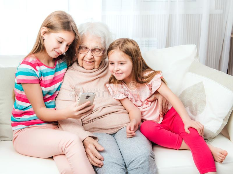 Glimlachende kleindochters met groot-grootmoeder stock foto
