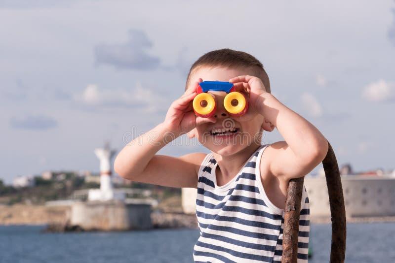 Glimlachende kleine jongen die de afstand onderzoeken door verrekijkers stock fotografie