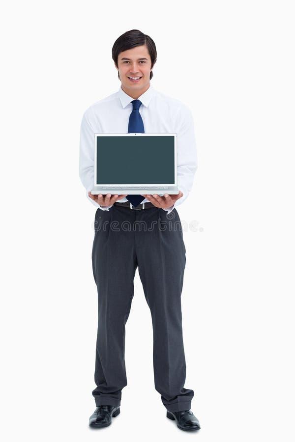 Glimlachende kleinhandelaar die het scherm van zijn laptop voorstelt royalty-vrije stock fotografie
