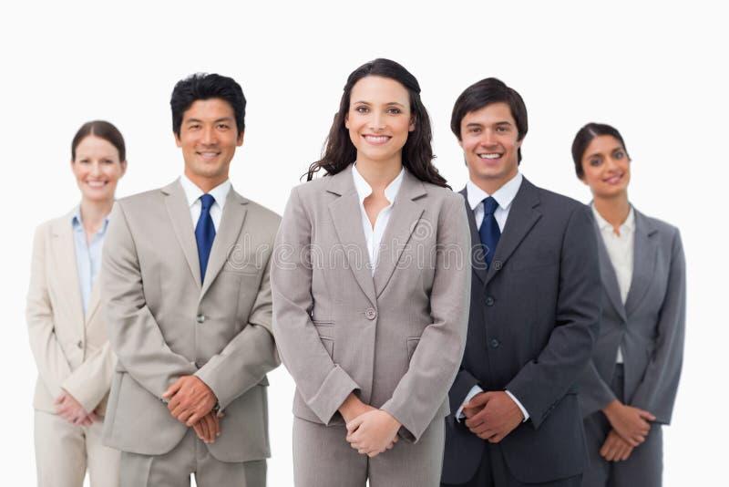 Glimlachende kleinhandelaarster die zich met haar collega's bevindt stock fotografie