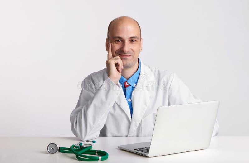 Glimlachende knappe arts met laptop stock foto