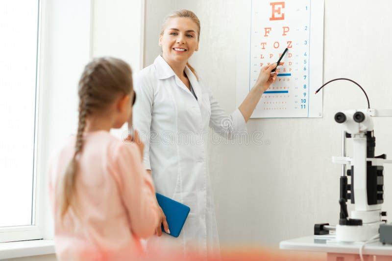 Glimlachende knappe blonde arts die capaciteiten van jong meisje onderzoeken stock fotografie