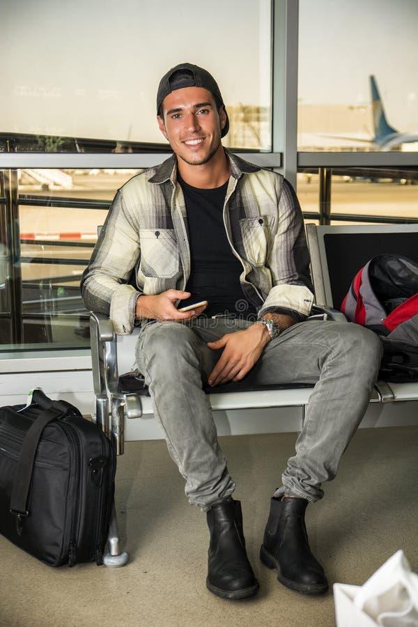 Glimlachende knappe jonge mens bij luchthaven stock afbeelding