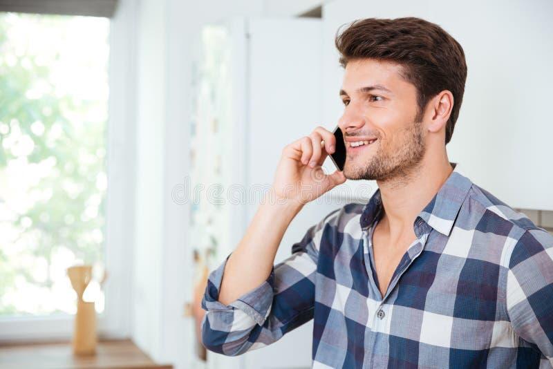 Glimlachende knappe jonge mens die op mobiele telefoon thuis spreken royalty-vrije stock afbeeldingen