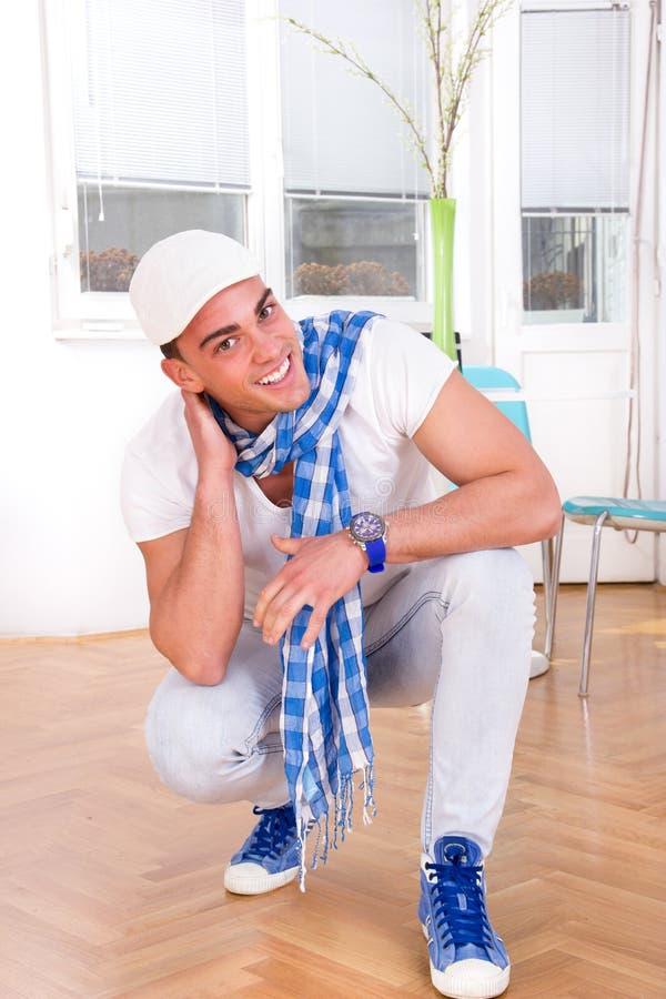 Glimlachende knappe maniermens met een sjaal en een wit GLB stock afbeeldingen