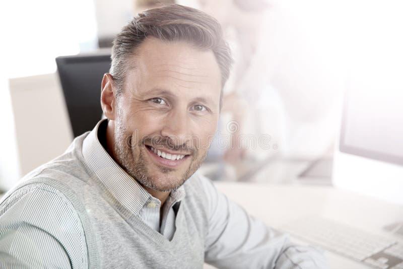 Glimlachende knappe mens op kantoor stock fotografie