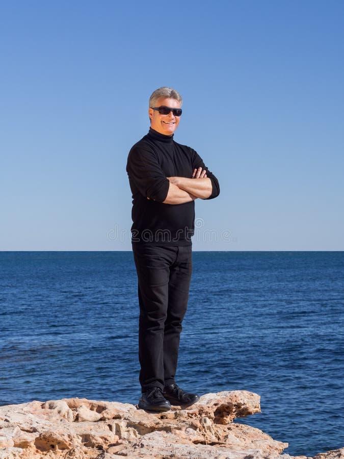 Glimlachende knappe zekere rijpe mens bij de kust royalty-vrije stock foto
