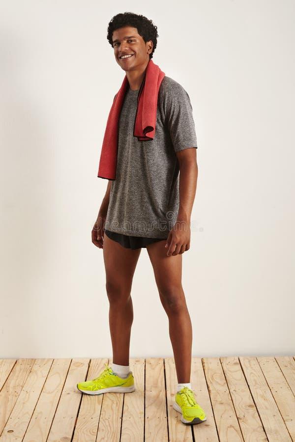 Glimlachende knappe zwarte atleet met een handdoek over zijn hals stock afbeelding