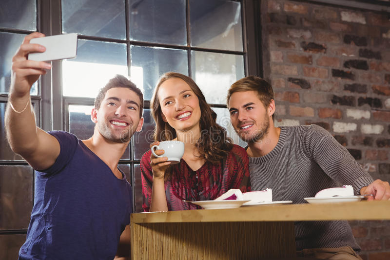 Glimlachende koffie hebben en vrienden die selfies nemen royalty-vrije stock fotografie