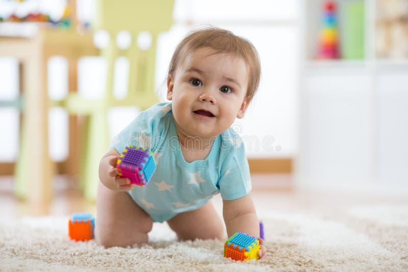 Glimlachende kruipende babyjongen op woonkamervloer, Kaukasisch kind stock fotografie