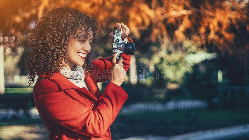 Glimlachende krullende vrouw met uitstekende camera royalty-vrije stock afbeelding