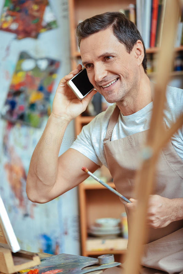 Glimlachende kunstenaar die op cellphone in het schilderen van studio spreken royalty-vrije stock fotografie