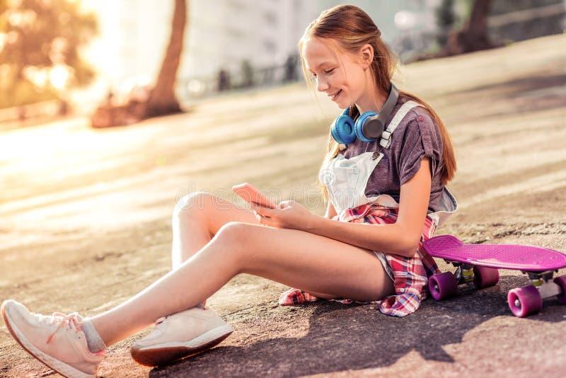 Glimlachende langharige tiener die met sociale media worden onderhouden stock afbeeldingen