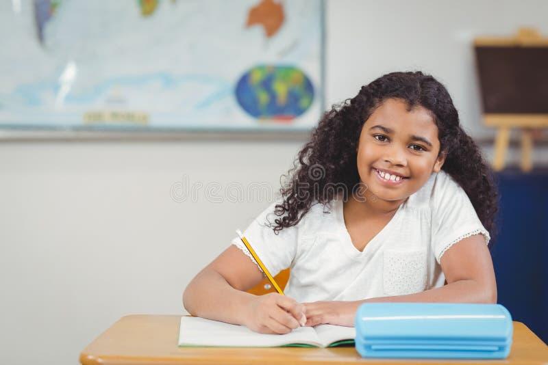 Glimlachende leerling die bij haar bureau in een klaslokaal werken stock fotografie