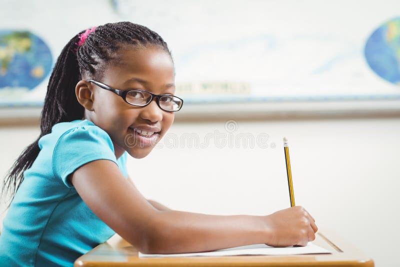 Glimlachende leerling die bij haar bureau in een klaslokaal werken stock afbeelding