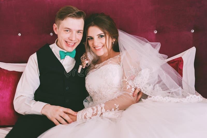 Glimlachende leuke bruid en bruidegom op karmozijnrood bed royalty-vrije stock afbeeldingen