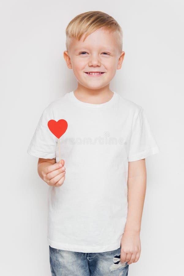 Glimlachende leuke jongen in witte t-shirt met rood hart royalty-vrije stock afbeeldingen