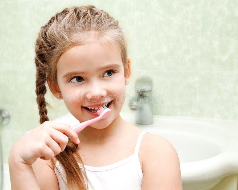 Glimlachende leuke meisje het borstelen tanden stock fotografie