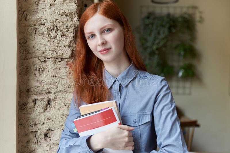 Glimlachende leuke schuwe jonge vrouw met lang rood haar die en boeken bevinden zich houden royalty-vrije stock foto
