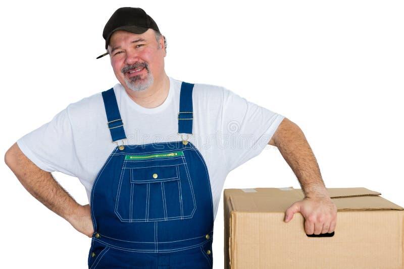 Glimlachende leveringsmens die zich door grote doos bevinden stock foto's