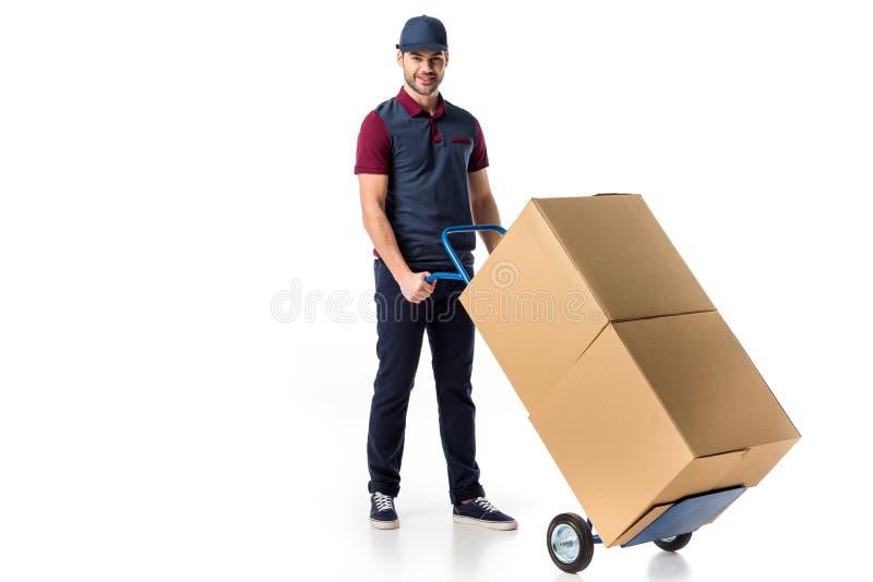 glimlachende leveringsmens in eenvormige duwende handvrachtwagen met kartondozen stock fotografie