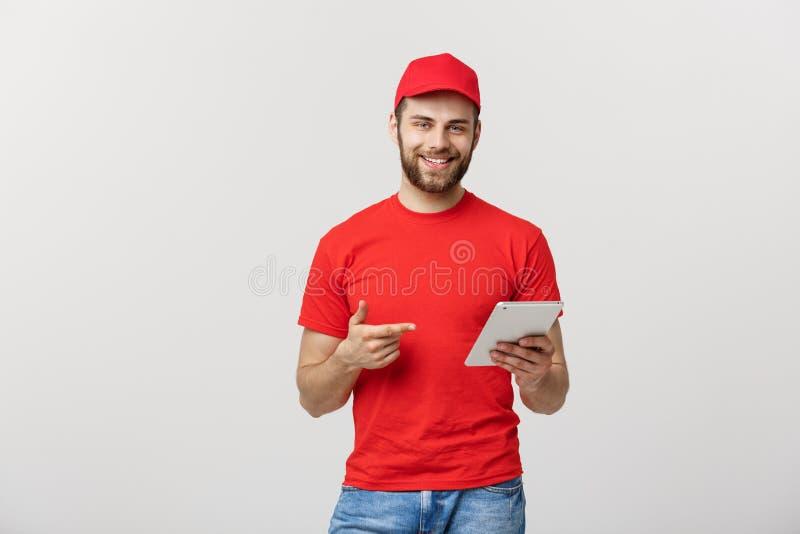 Glimlachende leveringsmens met tablet in studio Grijze achtergrond stock foto