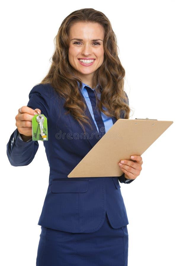 Glimlachende makelaar in onroerend goedvrouw die met klembordsleutels geven royalty-vrije stock afbeeldingen