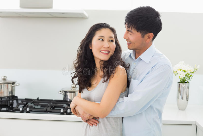 Glimlachende man die vrouw van erachter in keuken omhelzen stock afbeelding