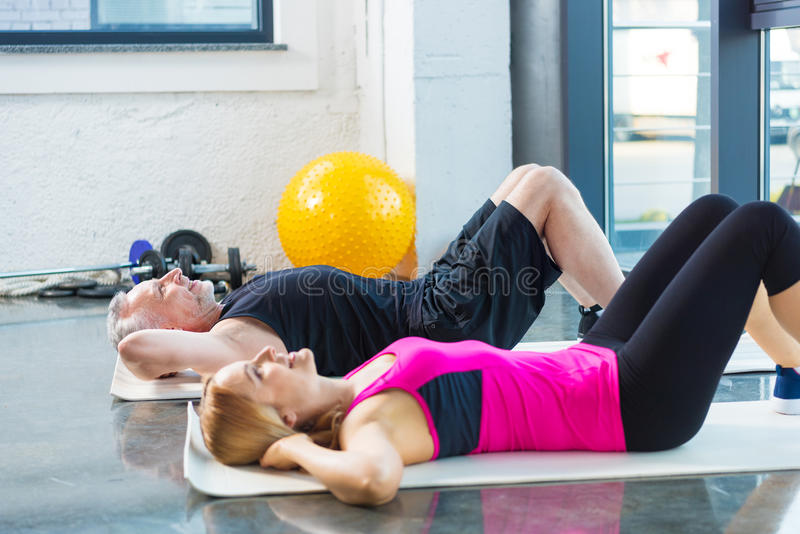 Glimlachende man en vrouw in sportkleding die abs in gymnastiek doen stock afbeeldingen