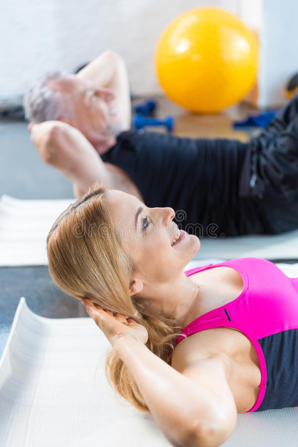 Glimlachende man en vrouw in sportkleding die abs in gymnastiek doen stock afbeelding