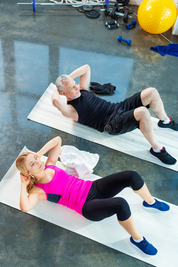 Glimlachende man en vrouw in sportkleding die abs in gymnastiek doen royalty-vrije stock afbeelding