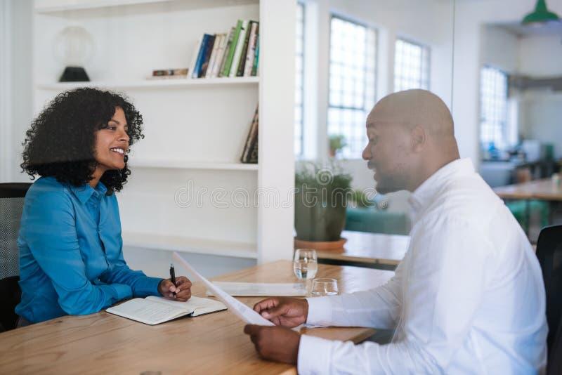 Glimlachende manager die een potentiële werknemer in haar bureau interviewen royalty-vrije stock foto's