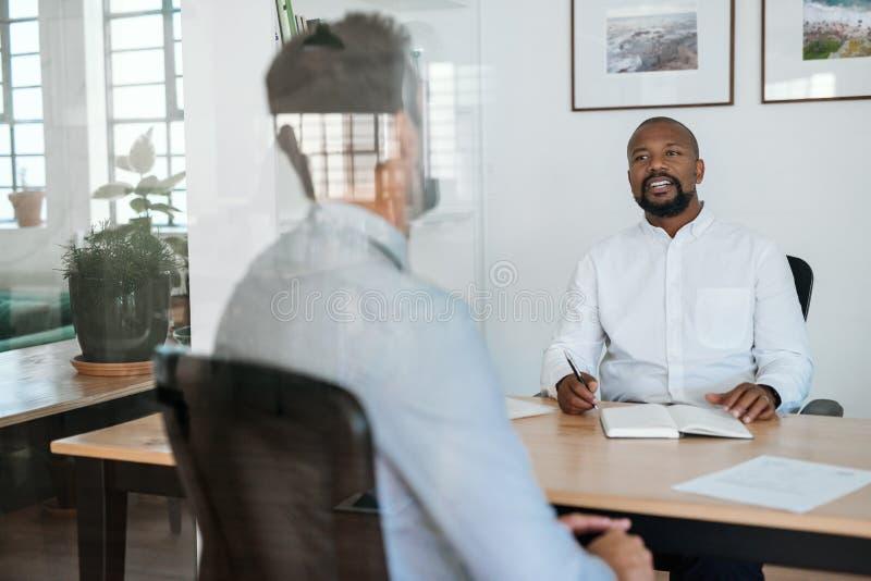 Glimlachende manager die een potenti?le werknemer in zijn bureau interviewen royalty-vrije stock afbeelding