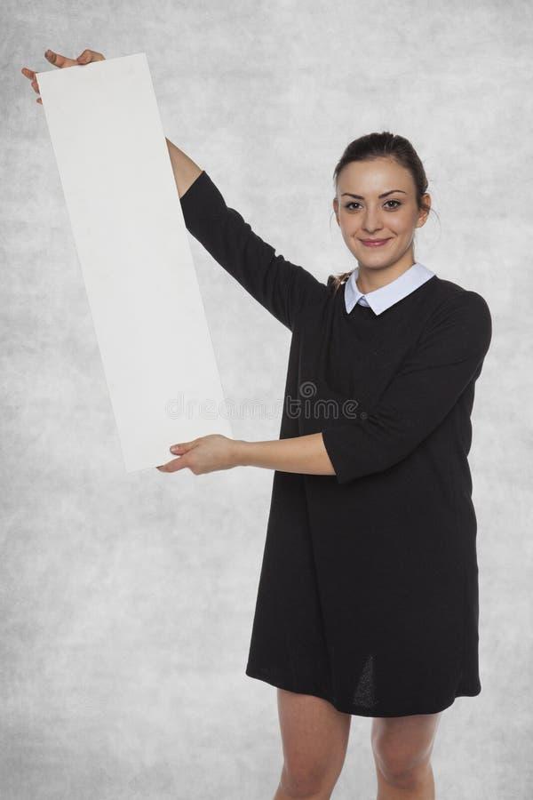 Glimlachende maniervrouw die een leeg aanplakbord, exemplaarruimte houden stock foto's