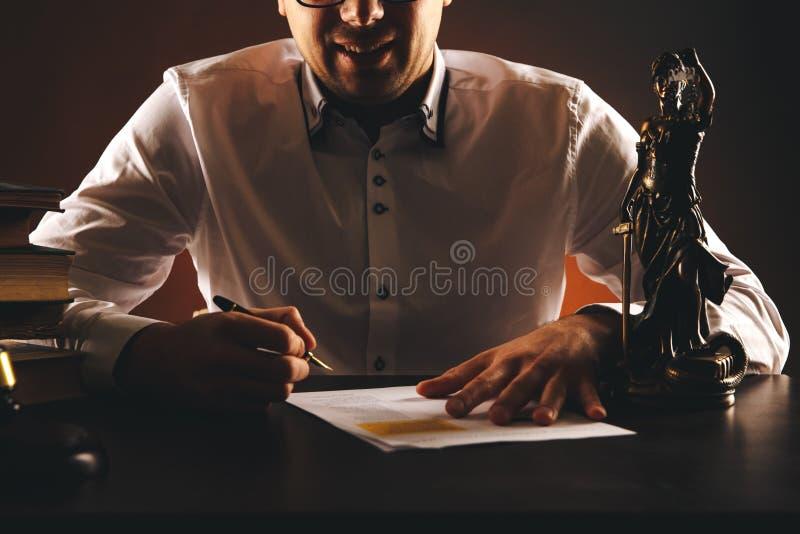 Glimlachende mannelijke advocaat op zijn bureau met administratie Weegschaal en houten hamer en boeken stock afbeelding