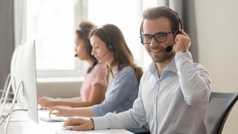 Glimlachende mannelijke call centreexploitant die in hoofdtelefoon camera bekijken stock fotografie