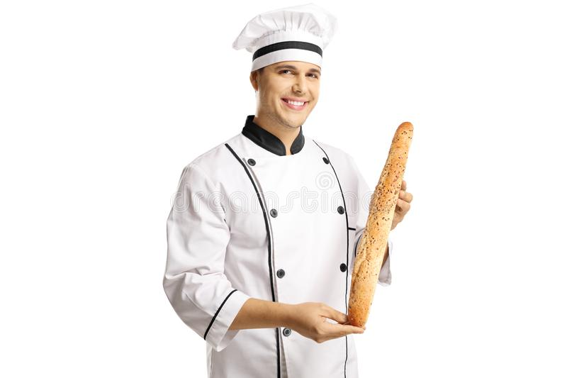 Glimlachende mannelijke chef-kok in een eenvormige holding een brood van baguettebrood royalty-vrije stock afbeelding