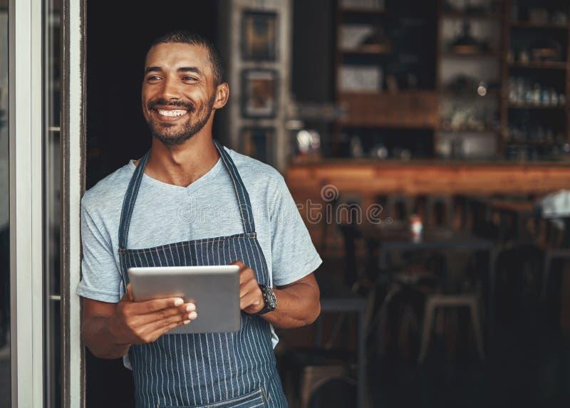 Glimlachende mannelijke eigenaar die zich bij de deuropening van zijn koffie bevinden royalty-vrije stock foto