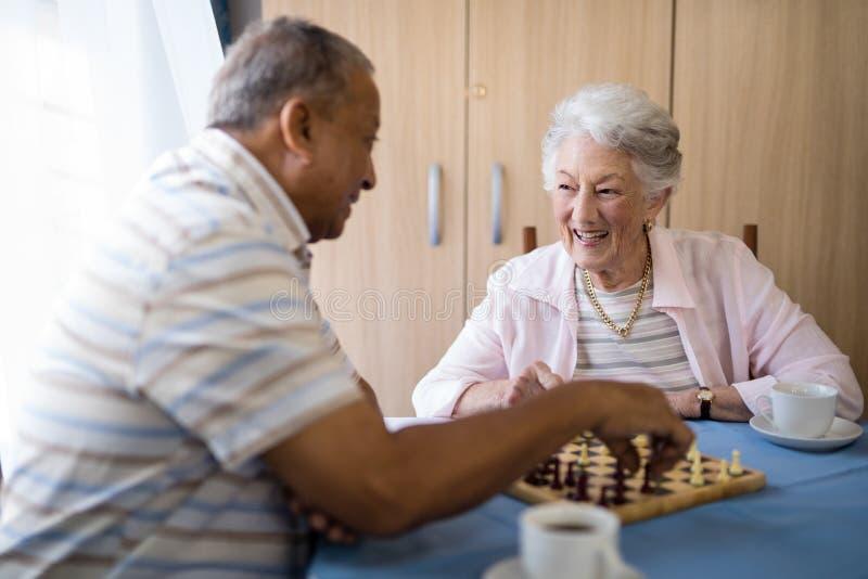 Glimlachende mannelijke en vrouwelijke oudsten die schaak spelen bij lijst stock fotografie