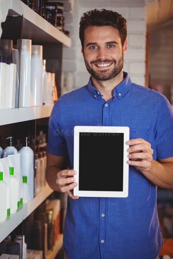 Glimlachende mannelijke kapper die digitale tablet tonen stock foto's