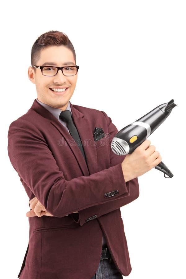 Glimlachende mannelijke kapper die een slagdroger houdt stock fotografie