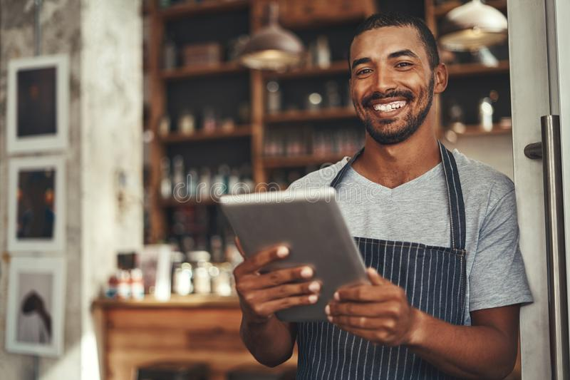 Glimlachende mannelijke koffieeigenaar die digitale tablet in zijn hand houden royalty-vrije stock foto