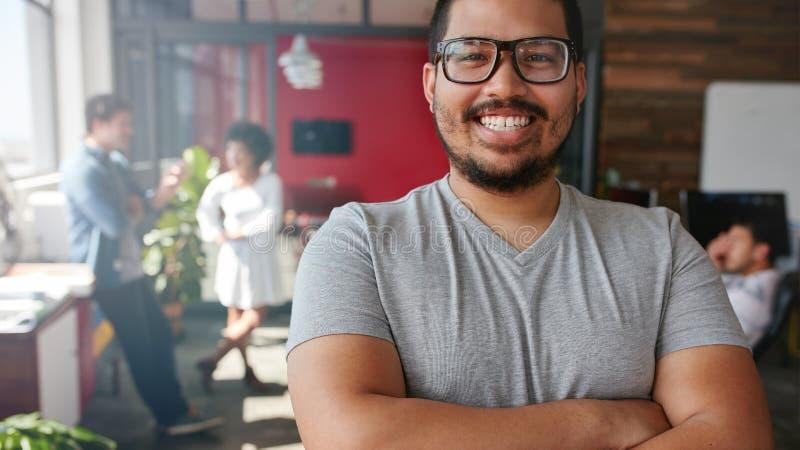 Glimlachende mannelijke ontwerper die camera op kantoor bekijken royalty-vrije stock afbeeldingen