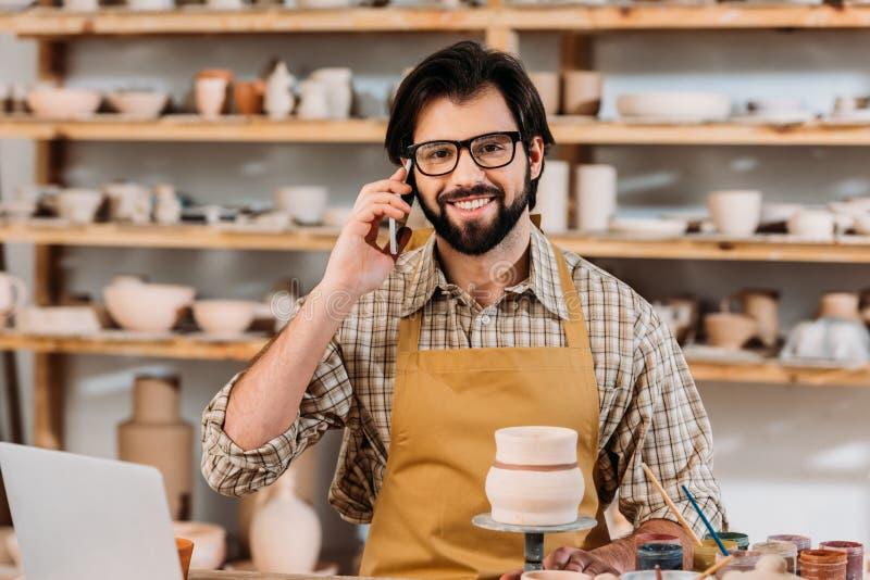 glimlachende mannelijke pottenbakker die op smartphone spreken royalty-vrije stock foto's
