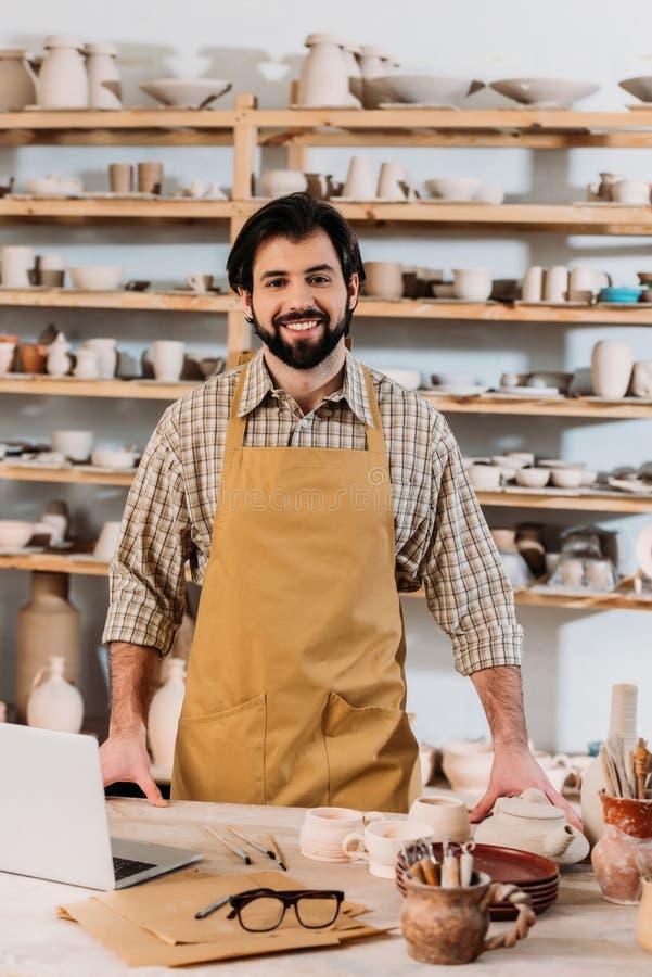 glimlachende mannelijke pottenbakker in schort die zich in workshop bevinden royalty-vrije stock foto