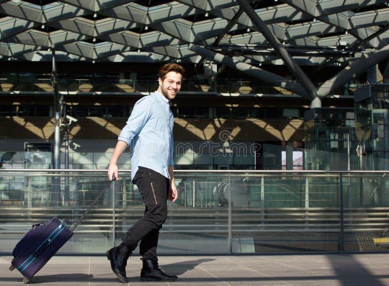 Glimlachende mannelijke reiziger die met koffer lopen stock afbeelding