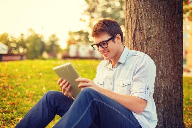 Glimlachende mannelijke student in oogglazen met tabletpc royalty-vrije stock afbeeldingen