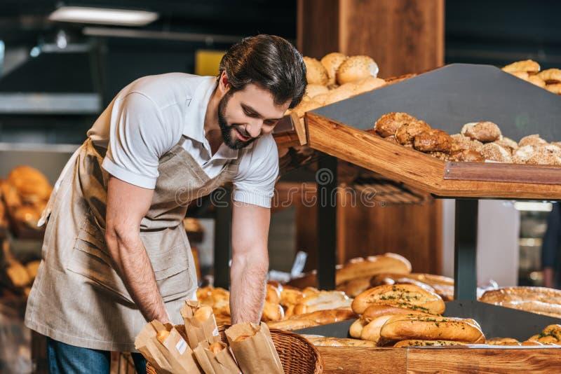 glimlachende mannelijke winkelmedewerker die vers gebakje schikken stock afbeeldingen
