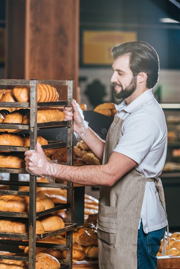 glimlachende mannelijke winkelmedewerker die vers gebakje schikken stock foto's